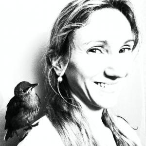 black and white image of a woman with long hair and a bird on her shoulder