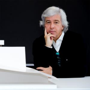 man with white hair wearing a white shirt with back sweater in front of a black background, leaning on a white table