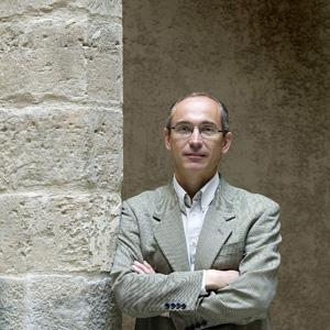 head and torso of a balding man wearing glasses and a suit jacket and white shirt, arms folded, standing in front of a stone and masonry wall.
