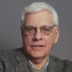 headshot of a man with white hair and glasses