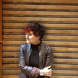 woman with red hair wearing a leather jacket and arms crossed in front of a wood-siding wall