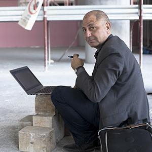 man sitting in front of a stack of cement bricks with a laptop balanced on top