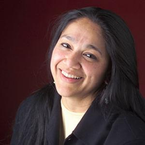 headshot of a woman with long dark hair wearing a black shirt