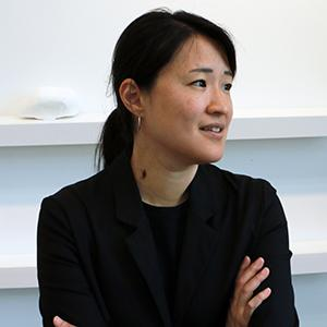 portrait of a woman with black hair wearing a black shirt and jacket with her arms crossed in front of her