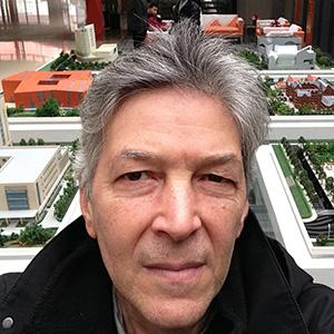 a man's face with architectural models in the background