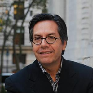 headshot of a man with dark hair and glasses wearing a jacket