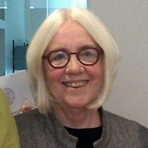 headshot of a woman with light blond hair and red glasses