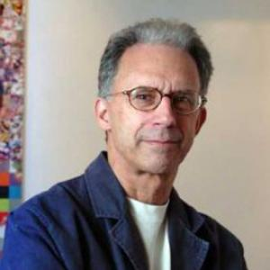 man with short grey hair and glasses in front of a multicolored painting
