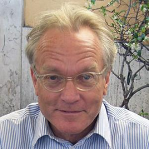headshot of a man with blond hair and glasses wearing a blue striped shirt