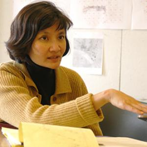 woman with bobbed dark hair wearing a tan sweater, sitting in front of pinned work turned sideways in dialogue
