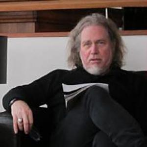man with longish gray hair and beard sitting in a chair with papers balanced on his leg