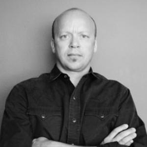 black and white headshot of a balding man wearing a black shirt
