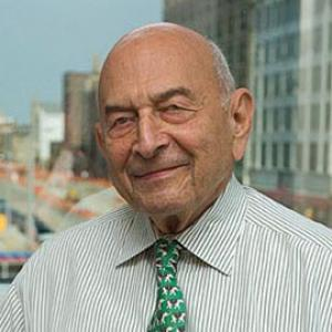 headshot of a bald man wearing a green striped shirt and tie with an urban landscape behind him