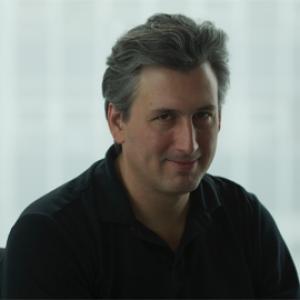 headshot of a man wearing a black button down shirt