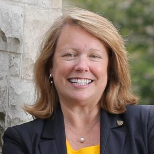 headshot of a woman with reddish hair wearing a blue blazer and yellow shirt