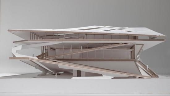 An architectural model made of light wood and white paneling.