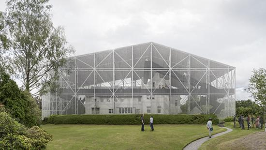 a large transparent superstructure covering a smaller building