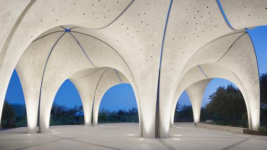 A concrete pavilion whose top extends upwards to create an irregular triangular grid roof.
