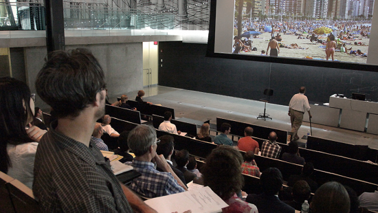 photo of people in lecture hall with photo in giant projector
