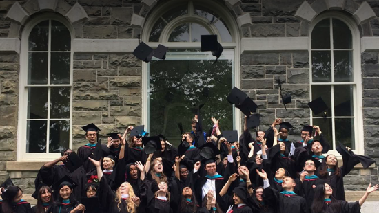 a group of people in graduation robes throwing their caps in the air in front of a stone building with windows