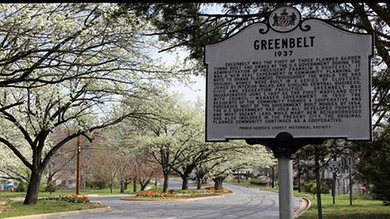 Historic marker sign for Greenbelt with a tree-lined street behind it