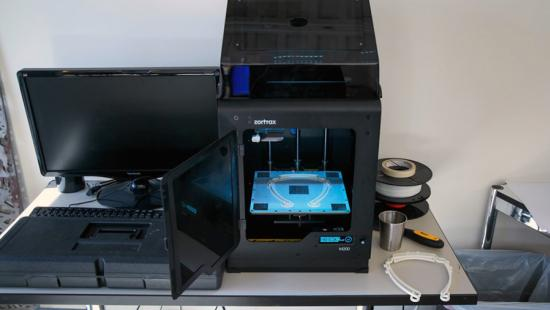 a laptop computer and digital laser cutting box sit on a table surface