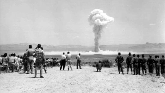 a black and white image of a nuclear cloud in the middle of the desert, the photograph taken behind the people looking on
