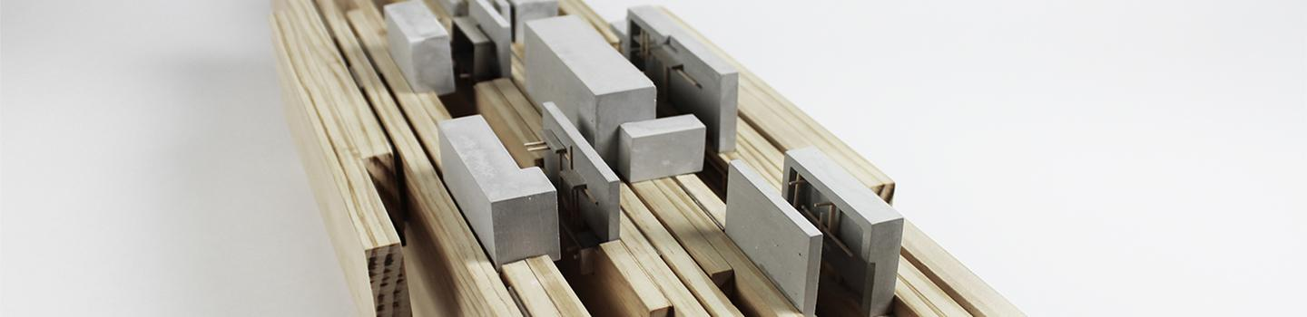 Photograph of model made of vertical wood boards as the site, with rockite boxes and basswood sticks embedded in between the boards and on top of them.