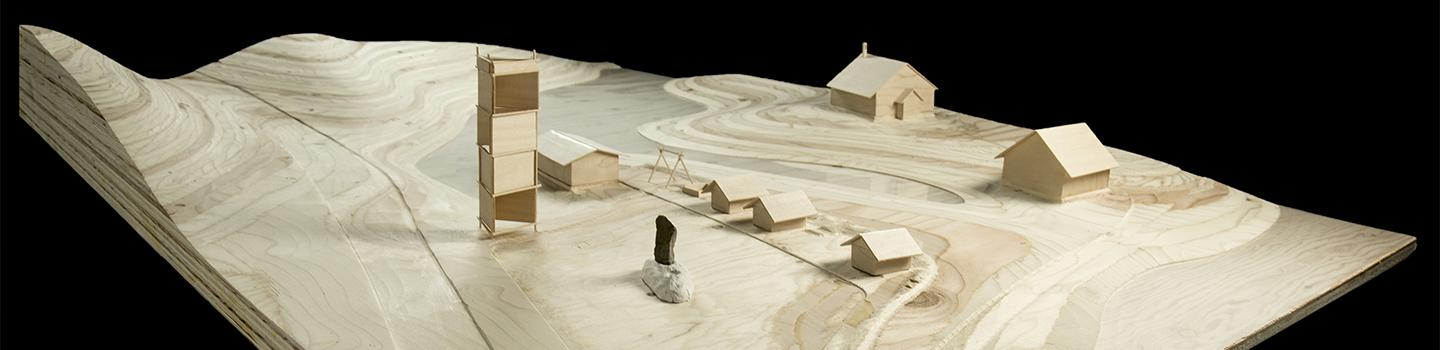 Photograph of site model made of milled wood topology with basswood buildings.