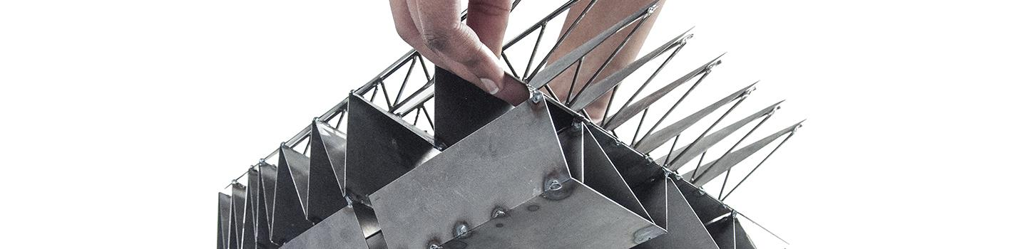 Photograph of hand placing top half of model made from thin-plate bended and welded steel onto bottom half of model.