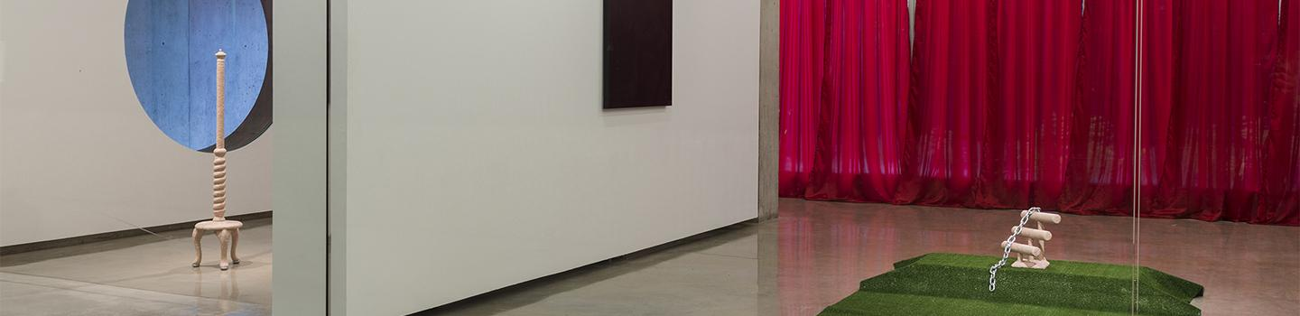 A white wall separating a tan unfinished coat rack, a very dark image, red curtains, and a tan abstract piece on green turf.