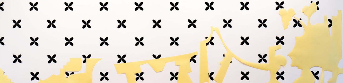 black stars patterned against a white background, yellow abstract shapes draped against it.