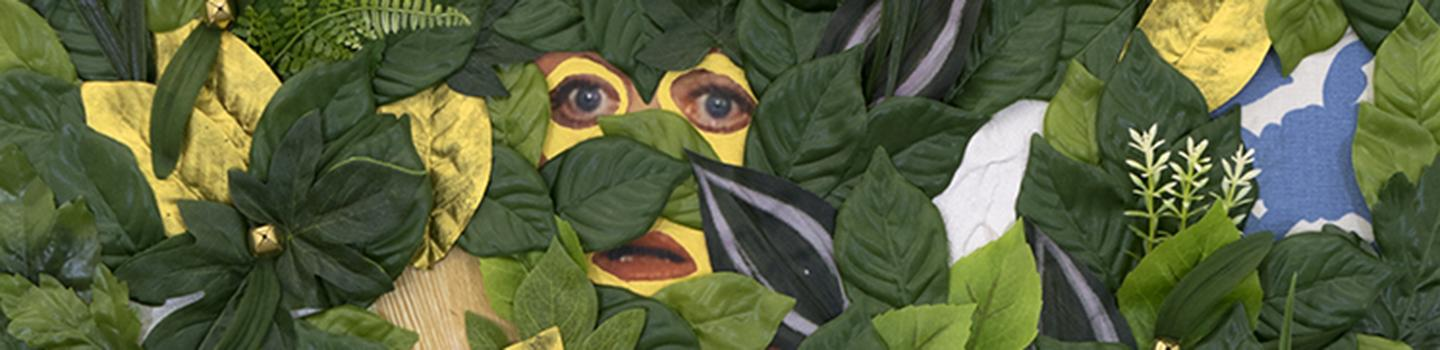 Green and yellow leaves covering a yellow painted face with eyes peeking out.