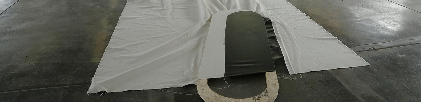 Image of a white cloth draped over an oval wooden shape with black painted on it.
