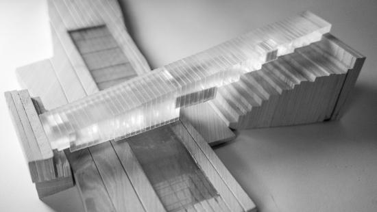 Black and white photograph of model made of wood for the site and a mass composed of vertical plexiglass layers glued together, with opaque masses embedded within.