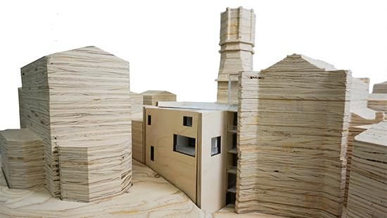 Photograph of model with site, including buildings, made of stacked plywood cut to shape, and with the project proposal made of thinner boards with rectangular perforations on the walls and white material on the inside.