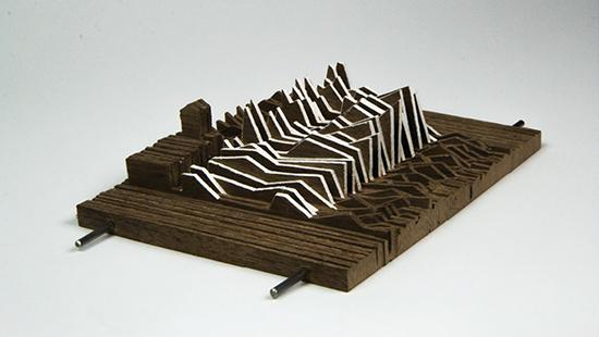 Photograph of model made from vertical strips of chipboard stacked together to form a topological mass, strung together by two metal rods, with a portion in the center showing more extreme angular profiles having strips of white paper bridging between the chipboard.