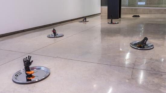 Six silver platters on a cement floor with black hands and feet on each one along with a red or orange colored pepper.