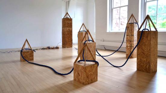 Wooden obelisk statues of various size with blue rope connecting them together in a white room.