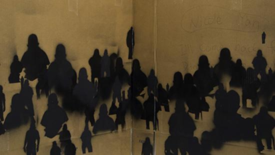 Black spray painted figures on cardboard.