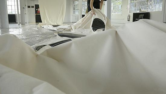 artist laying out large sheets of white fabric on the floor.