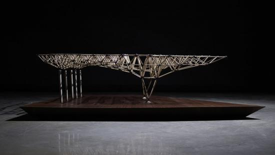 Architectural model constructed out of wood and elevated on a platform.
