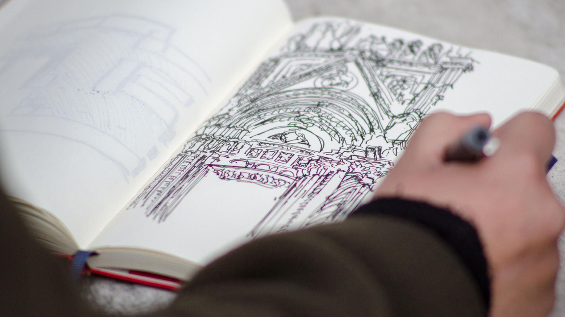 Hand sketching a Roman building in a sketchbook.