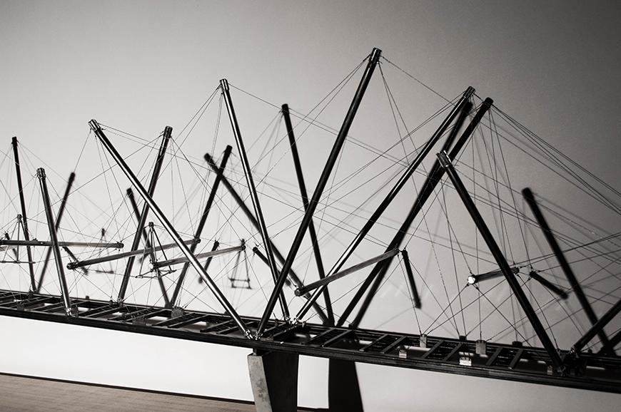 An architectural model of a suspended bridge structure.