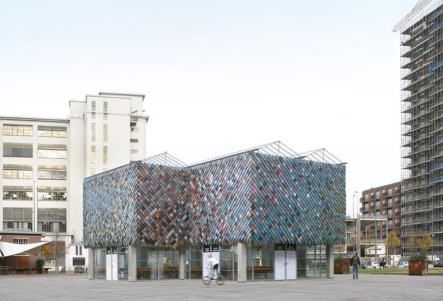 A pavilion with a pixel-like mosaic facade made from recycled plastic materials of varying colors.