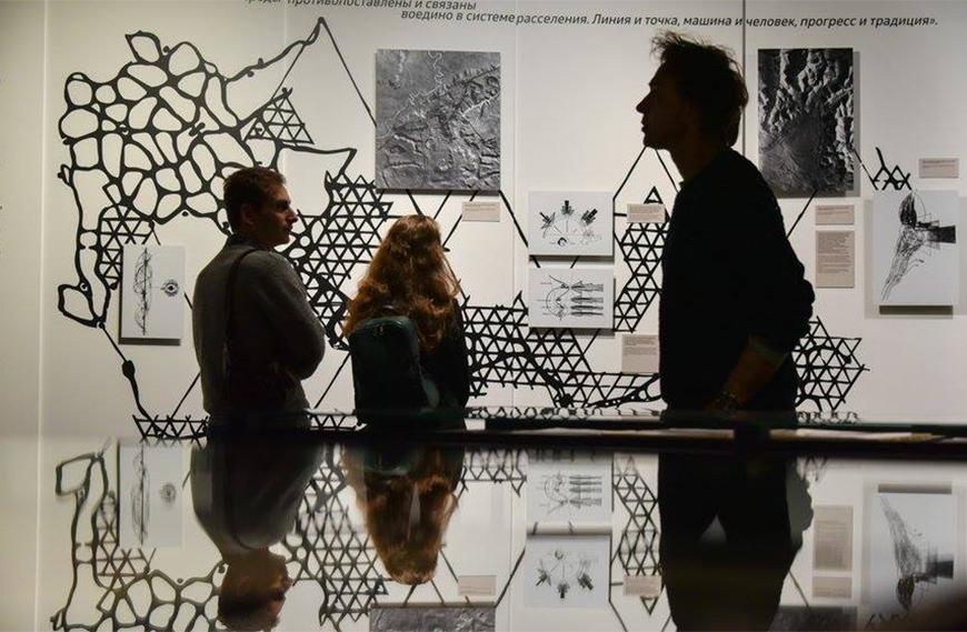 Three people examining an art exhibit.