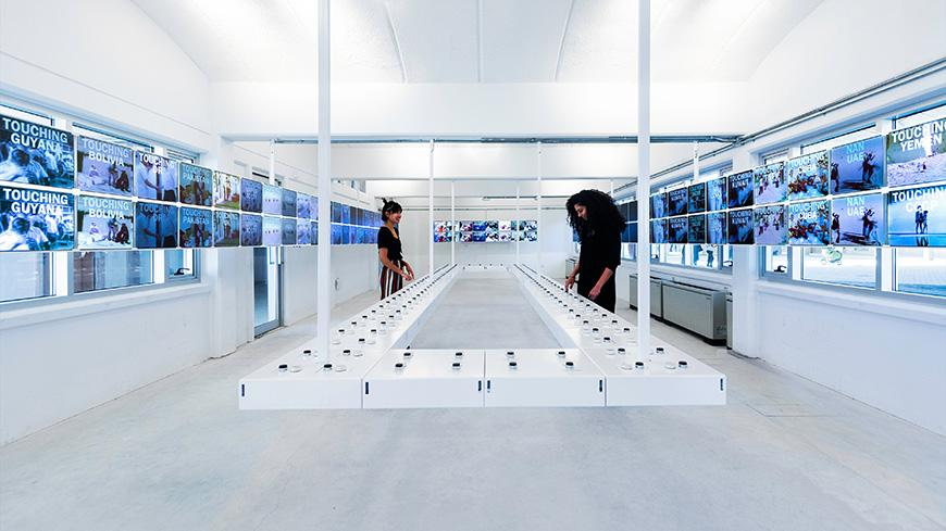 The modern interior of a building, whose walls are primarily white and overlaid with rows of television screens.