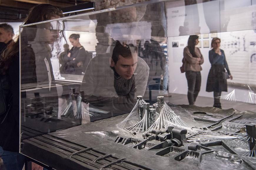 Two people examining an architectural design encased in glass with several other people admiring an exhibit.
