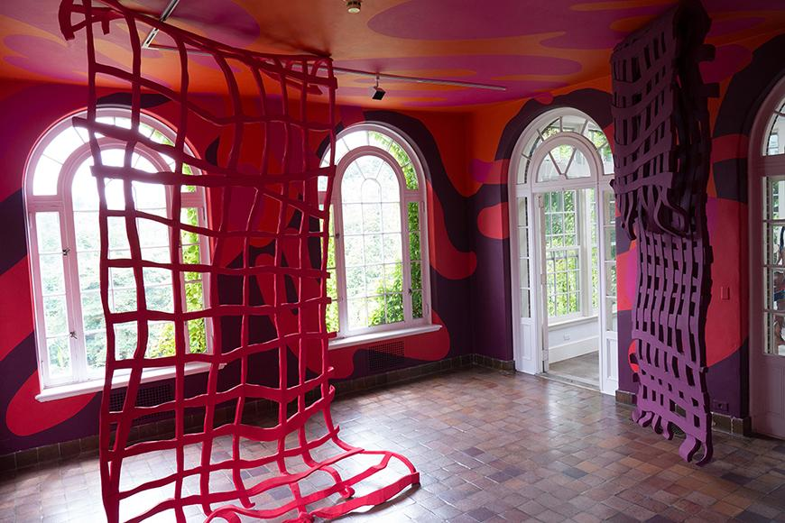 A room with red painted walls and two floor-to-ceiing red nets hung from the ceiling, and four arched windows