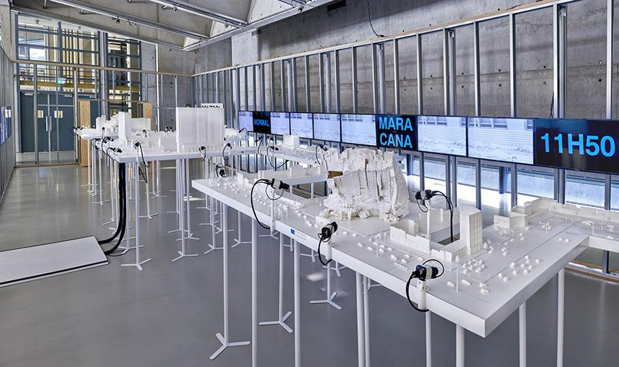The modern interior of a gallery space, whose center is occupied by white tables displaying architectural models.